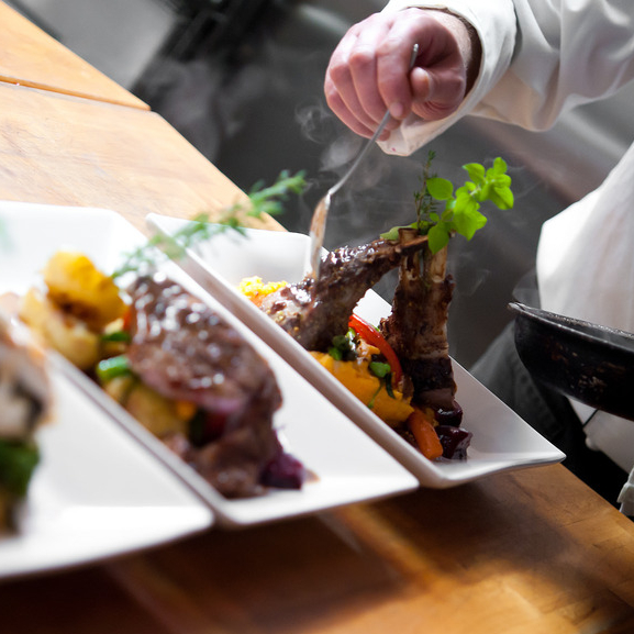 a chef plating three dishes with gourmet food