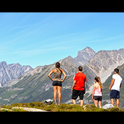 Group of people standing on mountain admiring the distant view.
