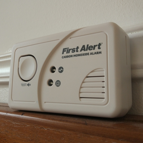 A white carbon monoxide detector sitting on a ledge