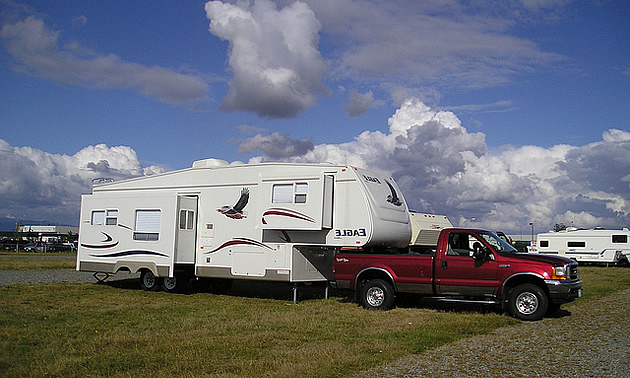 rv parked with a red truck hitched to it