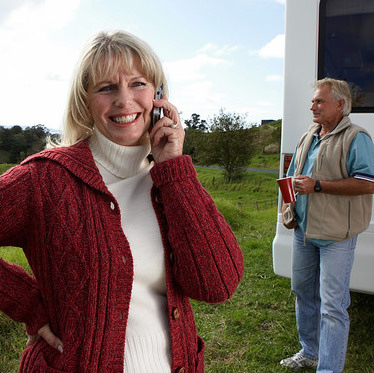 A smiling women pictured in the forground is talking on her cell phone while her husband, who is seen in the backround, is holding a cup of coffee next to their RV.