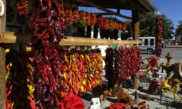Decorative strings of chiles hanging in an outdoor market.
