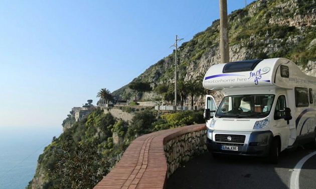 RV parked along high cliff-top road.