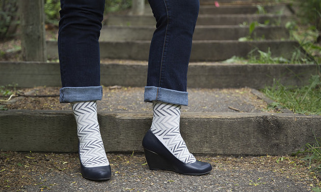 A women in rolled-up jeans, herring bone design compression socks and wedge healed shoes.