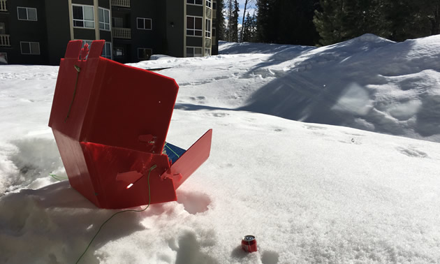 A red solar cooker is sitting in the snow outside an apartment building on a sunny winter day.
