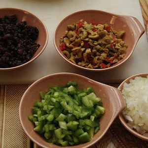 The fresh ingredients of this recipe shown chopped up in small bowls, green pepper, olives, raisins, onions and tomato sauce.