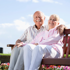 Older couple sitting on a bench in a garden