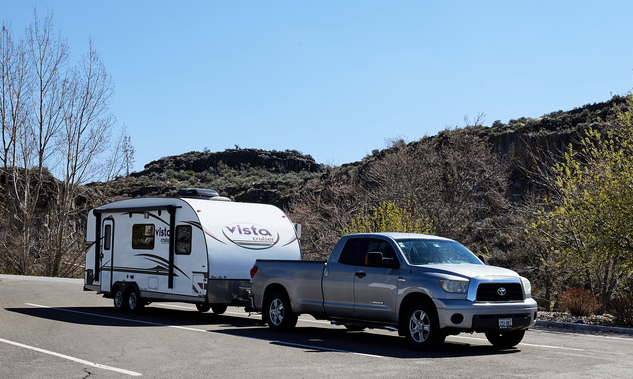 Truck and camper with small mountains in the background
