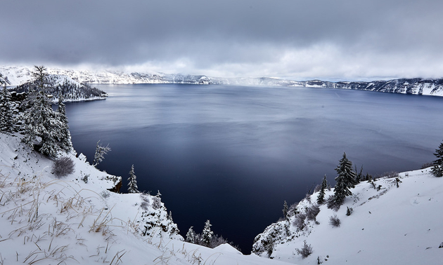 Crater lake with snowy trees and mist all around it