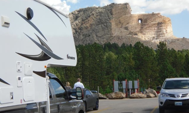 A side view of a truck and camper, with  Crazy Horse Memorial, Black Hill South Dakota, USA in the background.