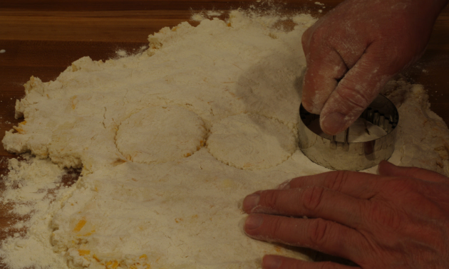 A person is cutting the dough with a biscuit cutter.