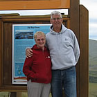 Husband and wife standing in front of an Arctic Circle sign