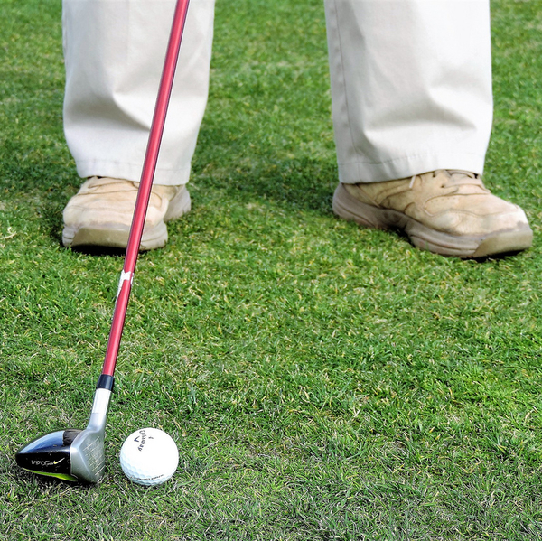 A man holding a golf club - about to hit the ball