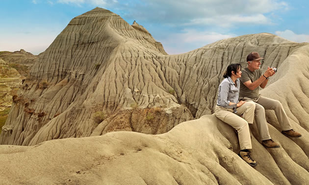 Two people sitting on rock formations at Dinosaur Provincial Park in Alberta.