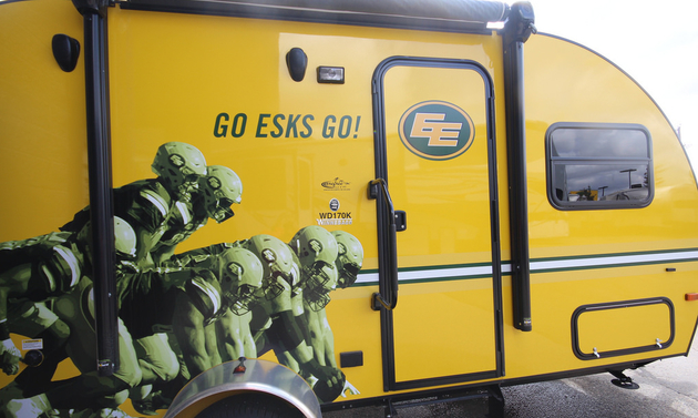 a yellow RV with promotional logos for the Eskimos