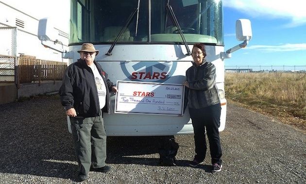 Duane and Linda Pilson with a cheque for STARS air ambulance.