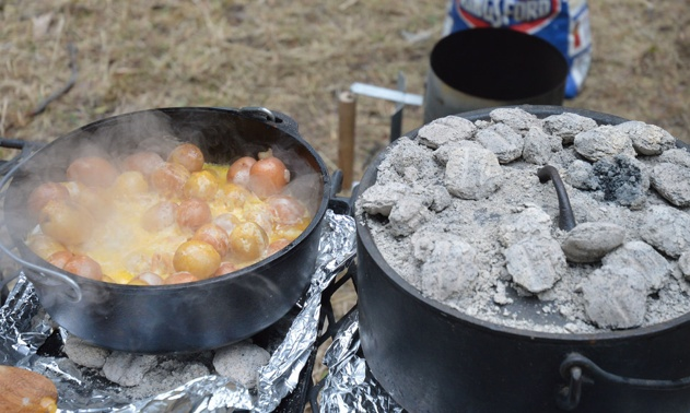 Two dutch ovens on a grate.  One is open and shows a finished pot of potatoes, onions and cheese.  The other pot is closed and has briquettes on top.
