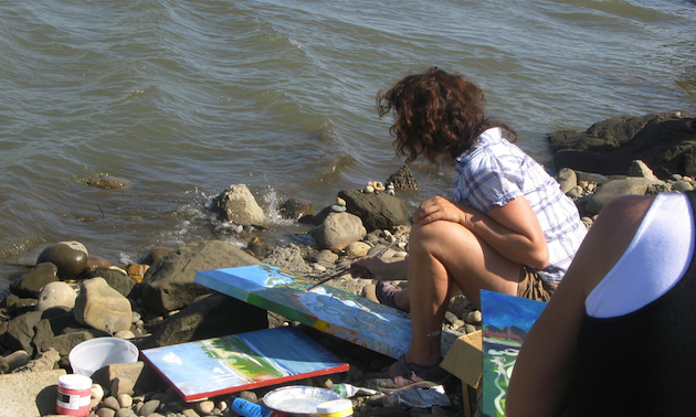 A woman painting beside a river.
