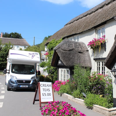 RV parked in front of quaint English thatched cottage.