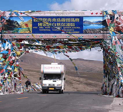The sign marking the 4,000 metre high entrance to the Qomolangma Nature Preserve is festooned with prayer flags.