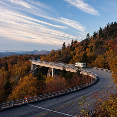 Picture of RV travelling along a winding highway in the autumn.