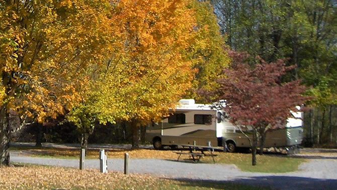 A picture of a RV parked at a campsite in the fall.
