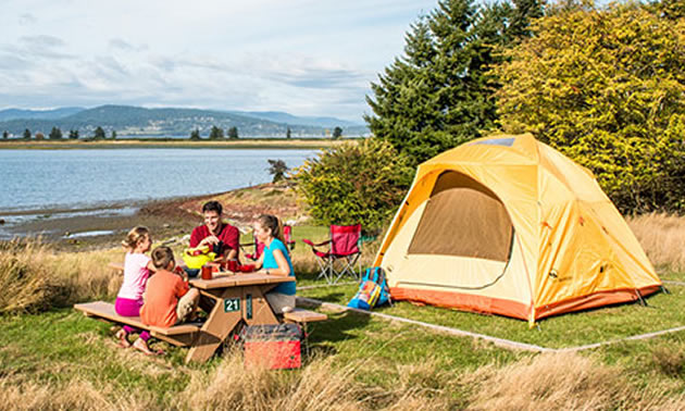 Family camping by lakeshore.