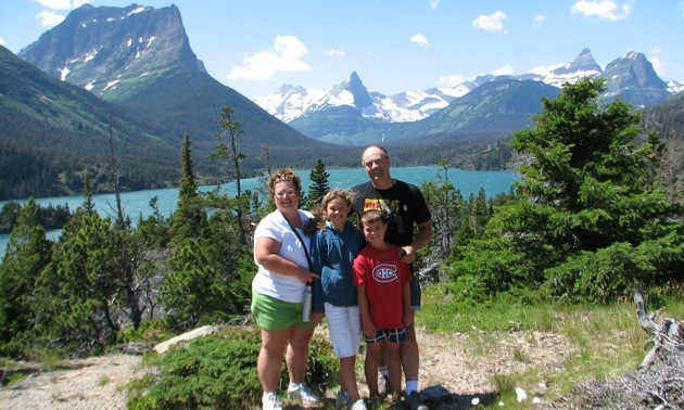 The Srubowich family with their backs to a view at the Going-to-the sun Road in Glacier Naional Park, Montana.