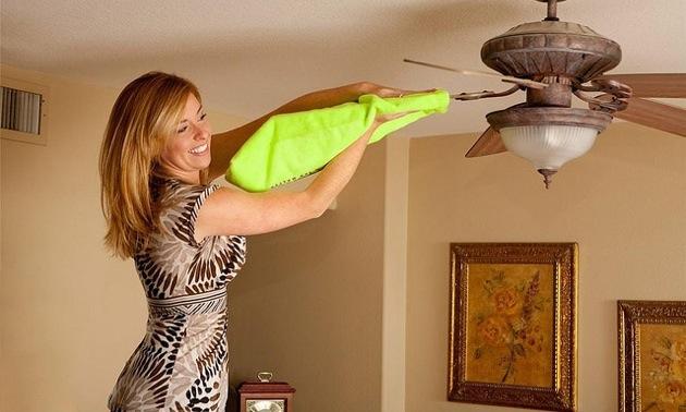 A women using FanBladeCleaner to wipe off a fan blade.