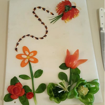 A tray of vegetables cut into a flower scene.