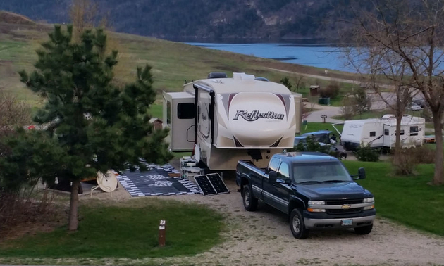 Shown is a campground in Fintry Provincial Park with a truck and fifth wheel parked.