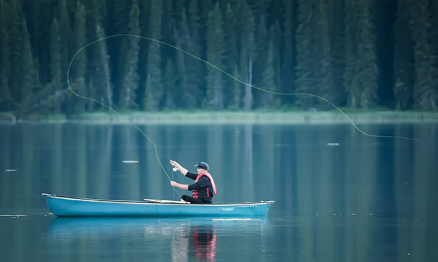 Peter Johnson sits in a canoe and casts into Fish Lake. White lines on the water surface are trout coming to the surface to eat flies.