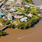 aerial view of the edge of a river and heritage park along the shore