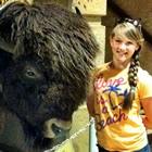 girl standing beside a stuffed buffalo