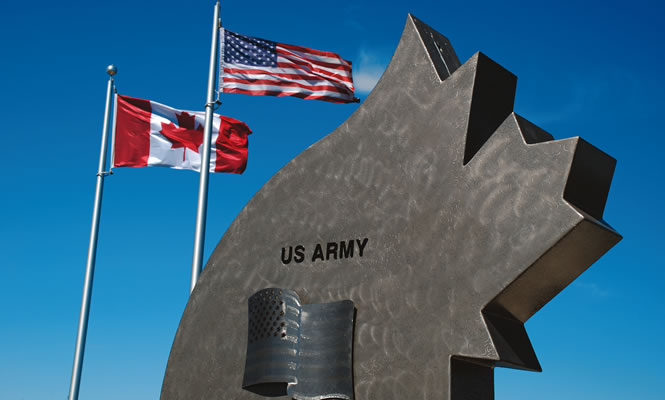 monument along with two flags, for USA and Canada