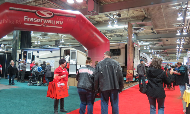 People at an RV show, looking at motorhomes