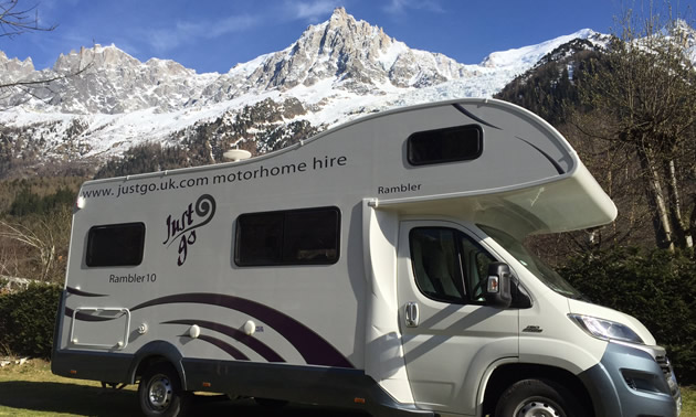 RV parked along side of road, with view of French Alps in background.