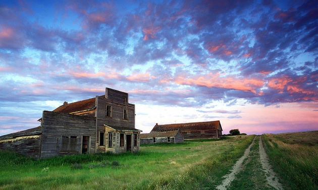 A Ghost Town in Saskatchewan with buildings on the left,  an old dirt tract on the right and a sky with clouds in different shades of pinks and reds.