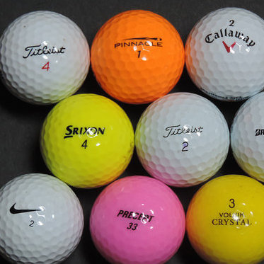 A selection of 9 golf balls of different colours, makes and sizes.