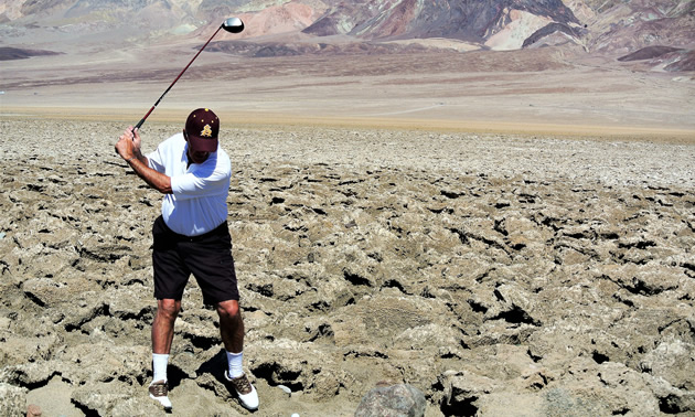 Golfer trying to hit ball in the midst of a field of rocks.