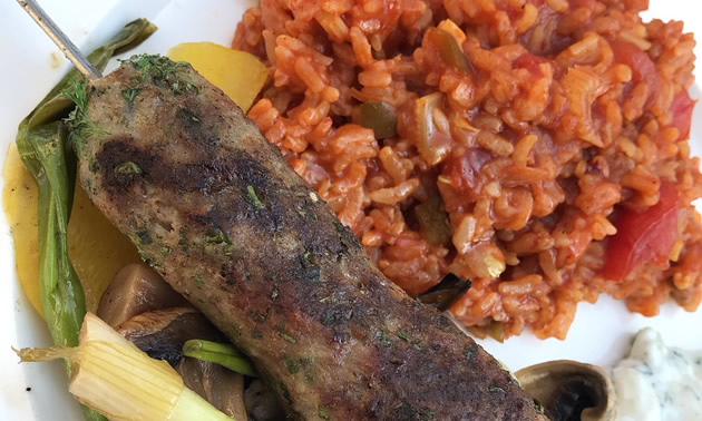 Plate with grilled sausage, vegetables and tomato rice.