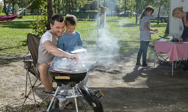 A father teaching his young son how to barbeque.