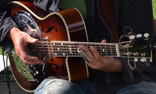 Man playing guitar at Harrison Mills