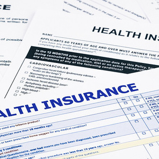 Numerous health insurance policies laying on a table.