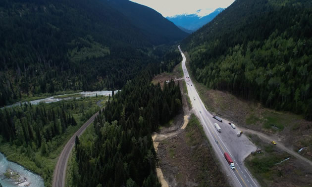 Aerial view of highway through mountains.