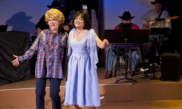 Two women are performing on a stage: one in a blue dress, the other in a plaid shirt and pants