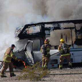 An RV on fire with a number of firefighters trying to put out the flames.