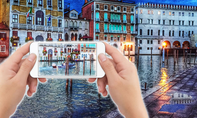 Pair of hands holding iphone with Venice canals in background.