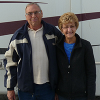 Senior couple stand with a large Everest RV behind them