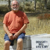 John Doughty sitting on some boxes of honey from his bees.